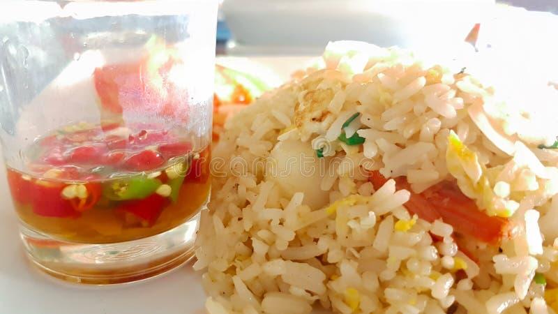 Соус рыб с красными и зелеными chili и жареными рисами на белой плите стоковое фото