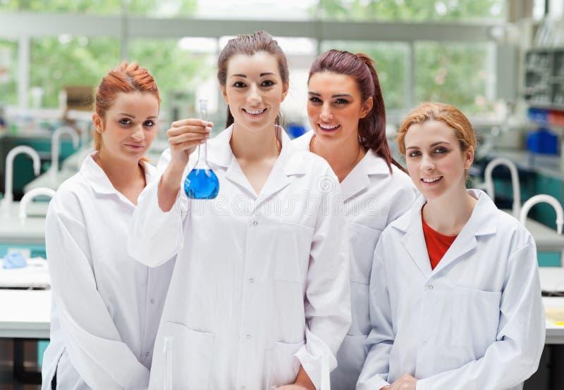 Соучастники лаборатории представляя с склянкой стоковое изображение