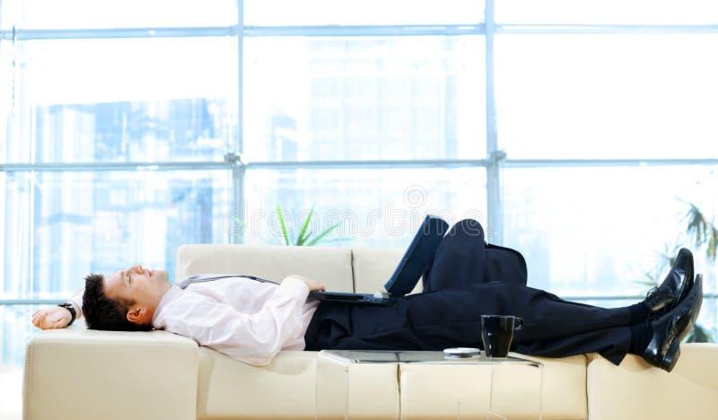 софа бизнесмена отдыхая стоковая фотография rf