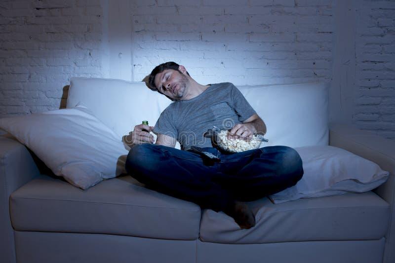 Софа молодого человека дома в живущей комнате спать пока смотрящ кино или спорт в ТВ на ноче стоковая фотография rf
