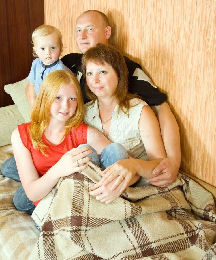 софа семьи ослабляя совместно стоковая фотография rf
