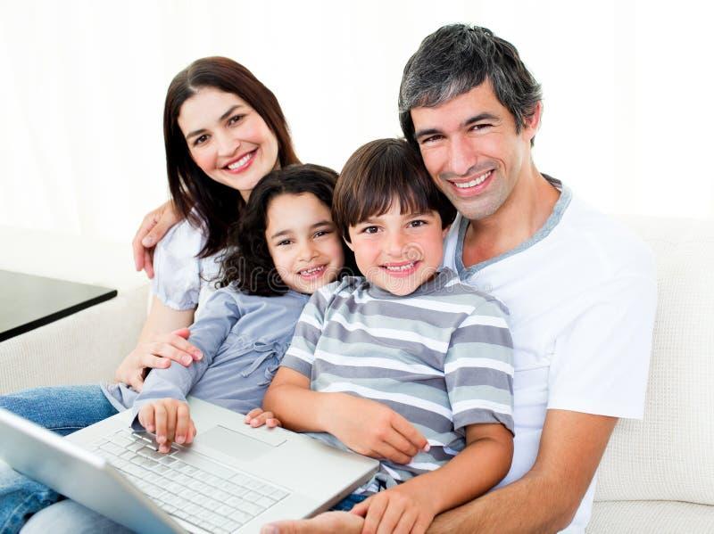 софа счастливой компьтер-книжки семьи сидя используя стоковое изображение