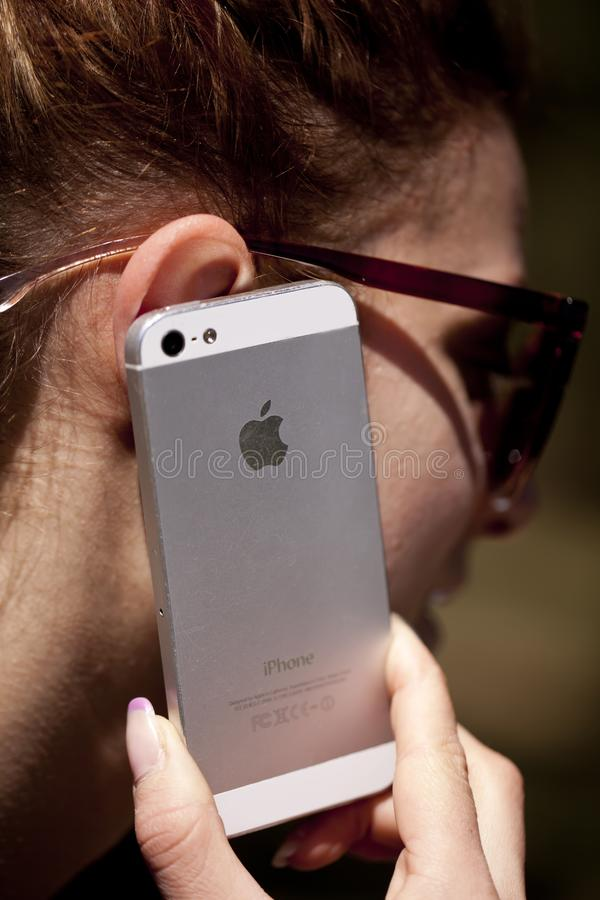 СОФИЯ, БОЛГАРИЯ - 17-ОЕ АПРЕЛЯ 2017: Женщина разговаривая с его телефоном надувательства Iphone Селективный фокус на логотипе Ябл стоковое изображение