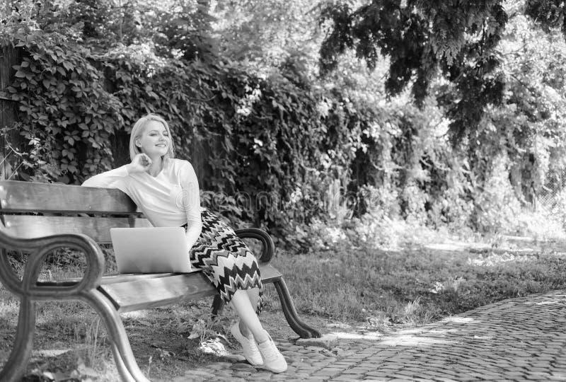 Сохраните ваше время с ходить по магазинам онлайн Покупки онлайн Девушка сидит стенд с тетрадью Женщина с ноутбуком в парке насла стоковые фото
