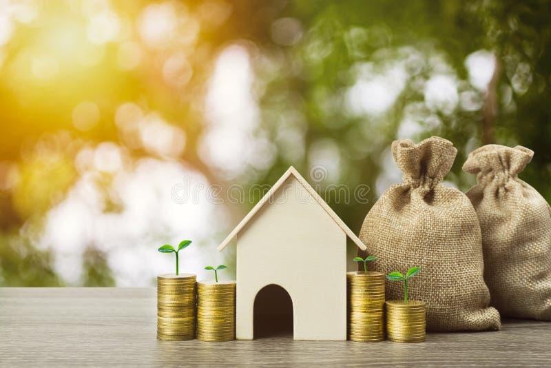 Сохраняя вклад денег или свойства или купить новую домашнюю концепцию Модель небольшого дома с заводом роста на стоге монеток и д стоковые изображения