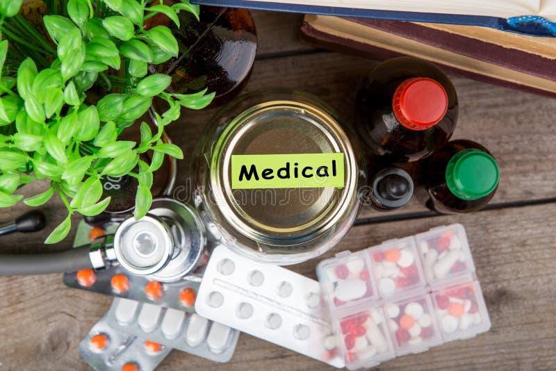 Сохраняя деньги для страхования здравоохранения - стекло, стетоскоп, таблетки и бутылки денег стоковые изображения rf