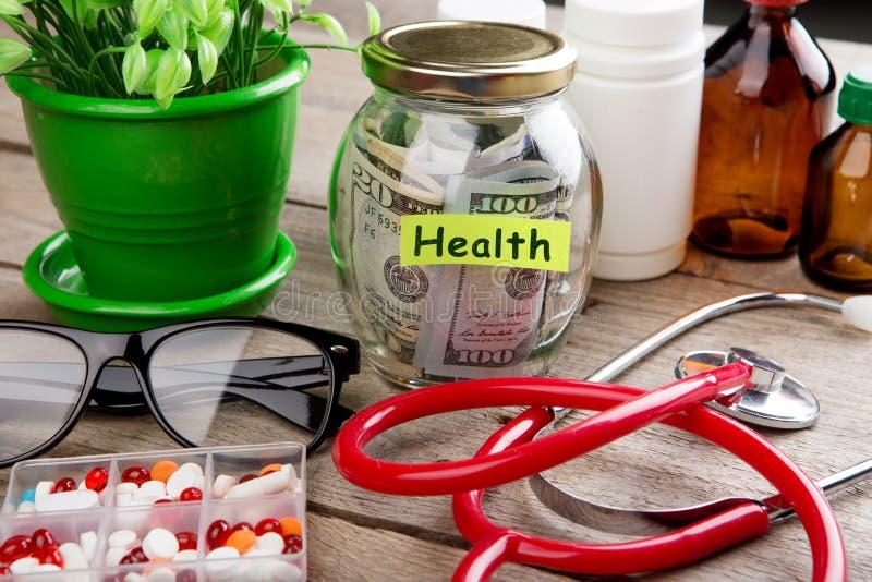Сохраняя деньги для страхования здравоохранения - стекло, стетоскоп, таблетки и бутылки денег стоковые фотографии rf