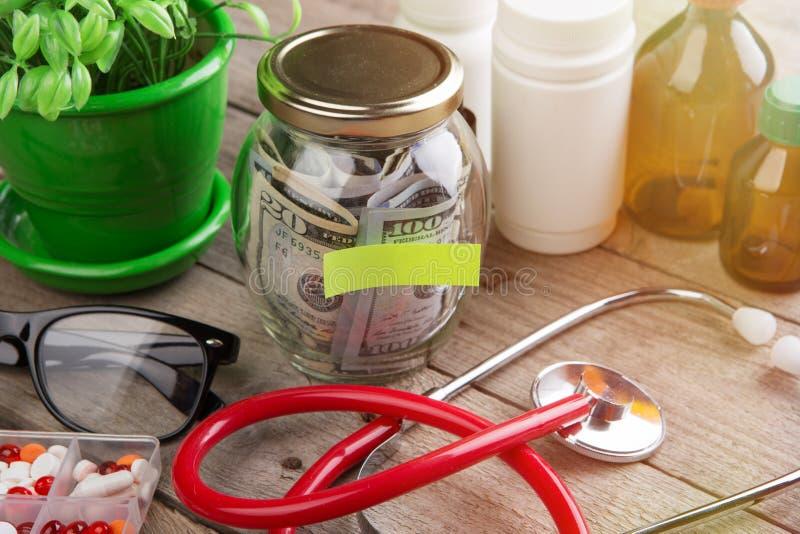 Сохраняя деньги для страхования здравоохранения - стекло, стетоскоп, таблетки и бутылки денег стоковые фото