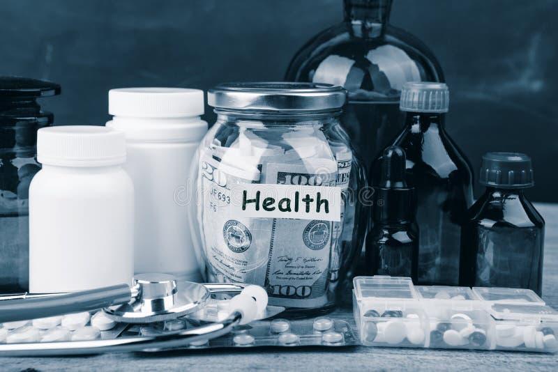 Сохраняя деньги для страхования здравоохранения - стекло, стетоскоп, таблетки и бутылки денег стоковое изображение