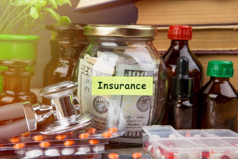 Сохраняя деньги для страхования здравоохранения - стекло, стетоскоп, таблетки и бутылки денег стоковое фото rf
