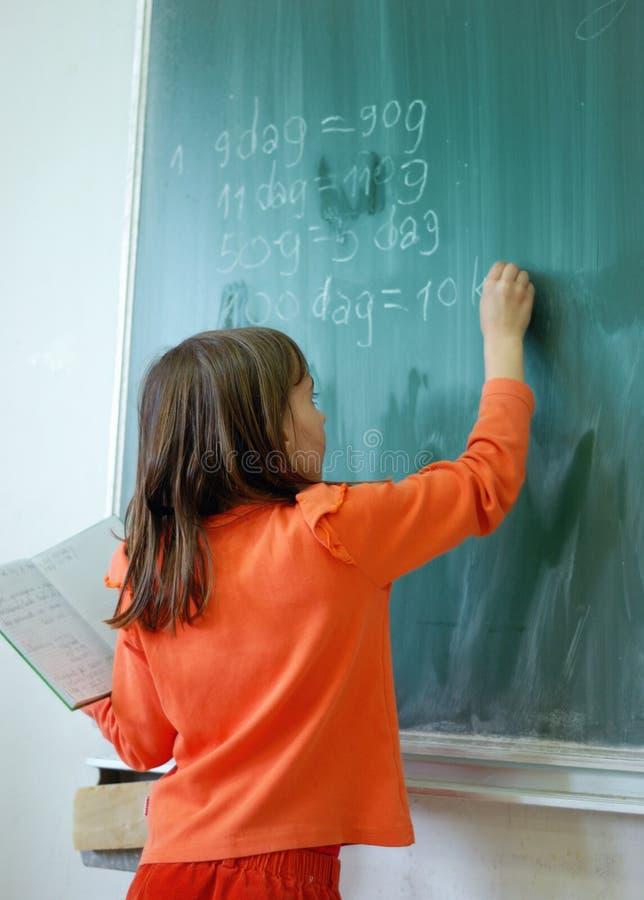 Сочинительство девушки на школьном правлении стоковая фотография rf