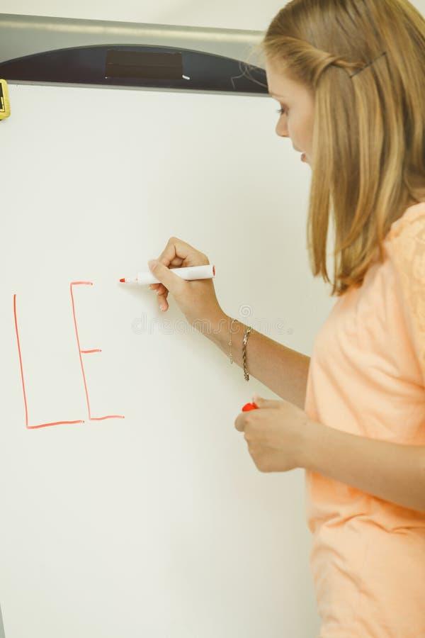 Сочинительство девушки студента уча слово на whiteboard стоковое изображение rf