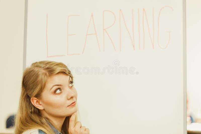 Сочинительство девушки студента уча слово на whiteboard стоковые изображения