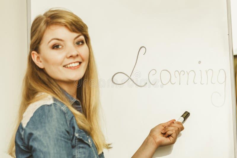 Сочинительство девушки студента уча слово на whiteboard стоковая фотография rf