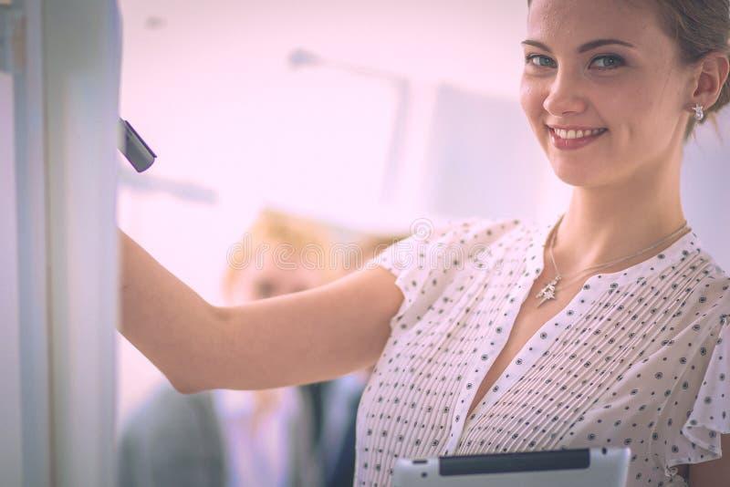 Сочинительство коммерсантки на flipchart пока дающ представление к коллегам в офисе стоковая фотография