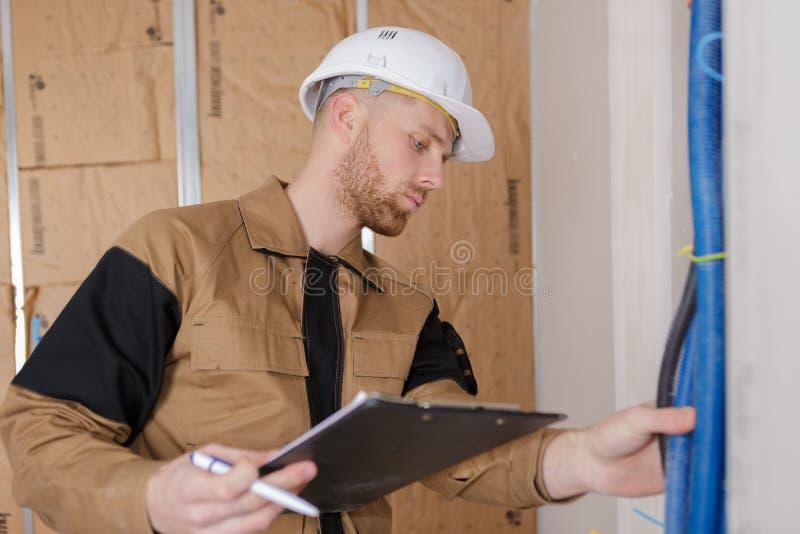 Сочинительство рабочий-строителя портрета молодое на доске сзажимом для бумаги стоковая фотография rf