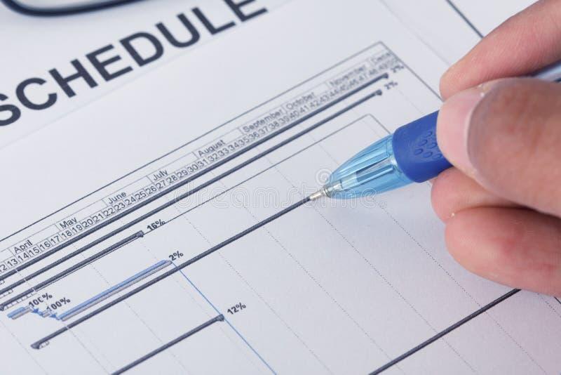 Сочинительство руки на документе расписания с ручкой и планово-контрольным графиком стоковые изображения rf