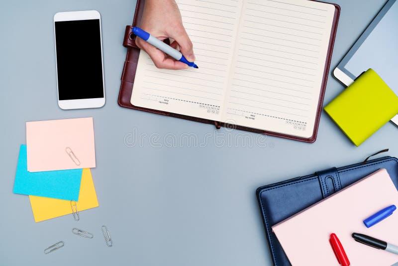 Сочинительство руки на тетради окруженной с аксессуарами офиса Взгляд сверху стола работы смартфон, книга, банк силы, ручка, план стоковая фотография rf