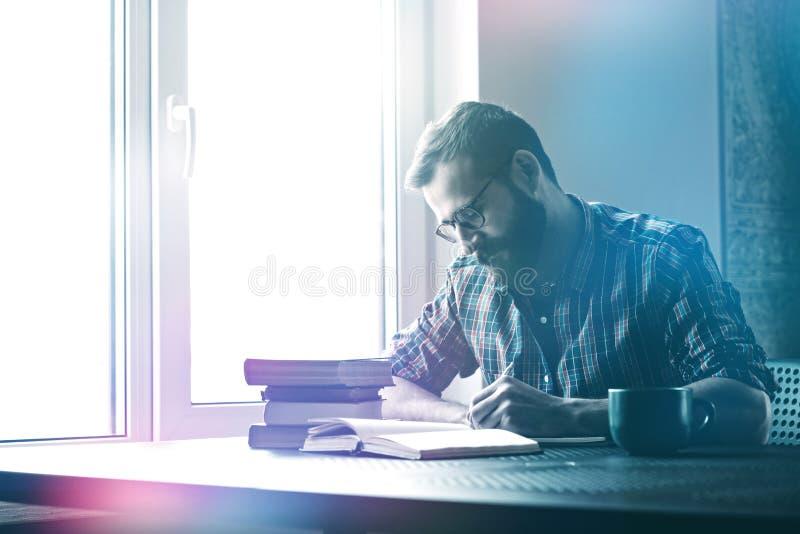 Сочинительство человека с книгами ручки и чтения стоковая фотография rf