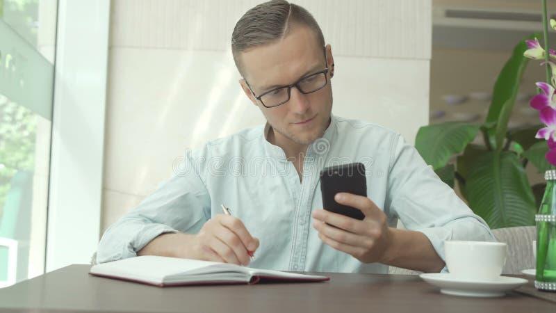 Сочинительство бизнесмена в ежедневных примечаниях плановика и проверки на smartphone стоковое фото rf