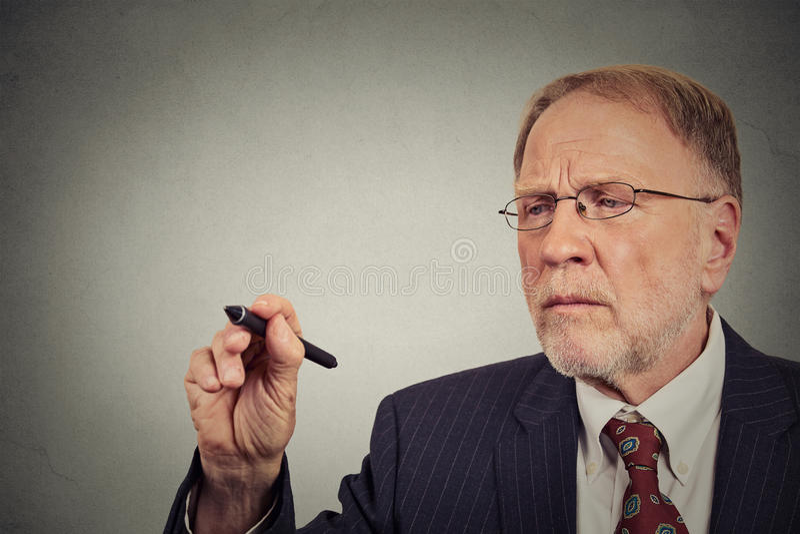 Сочинительство бизнесмена портрета крупного плана с ручкой стоковое фото