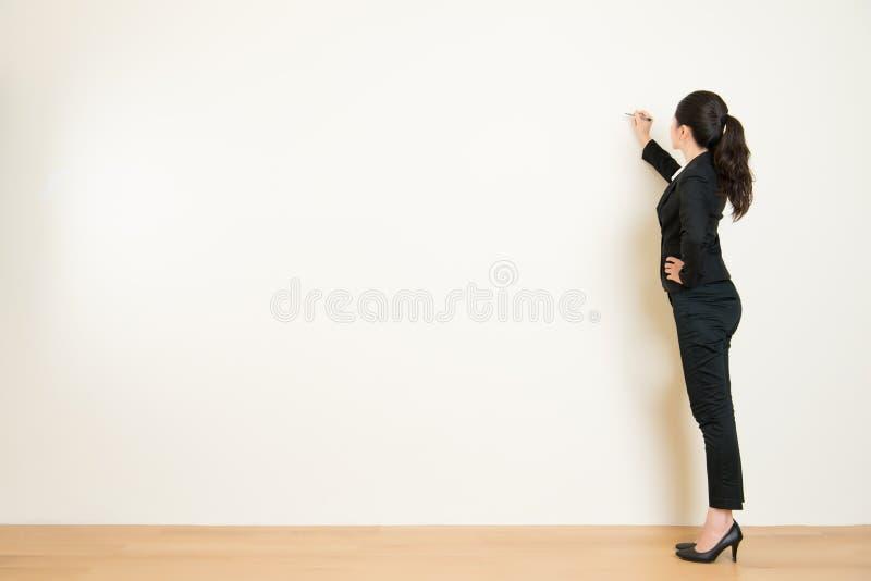 Сочинительство бизнес-леди что-то на белой стене стоковые изображения