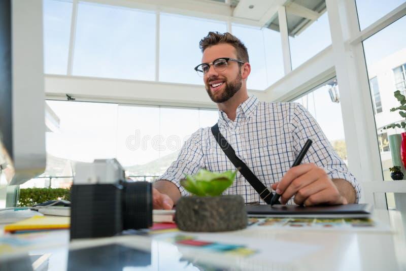 Сочинительство график-дизайнера на таблетке пока сидящ на столе стоковая фотография rf