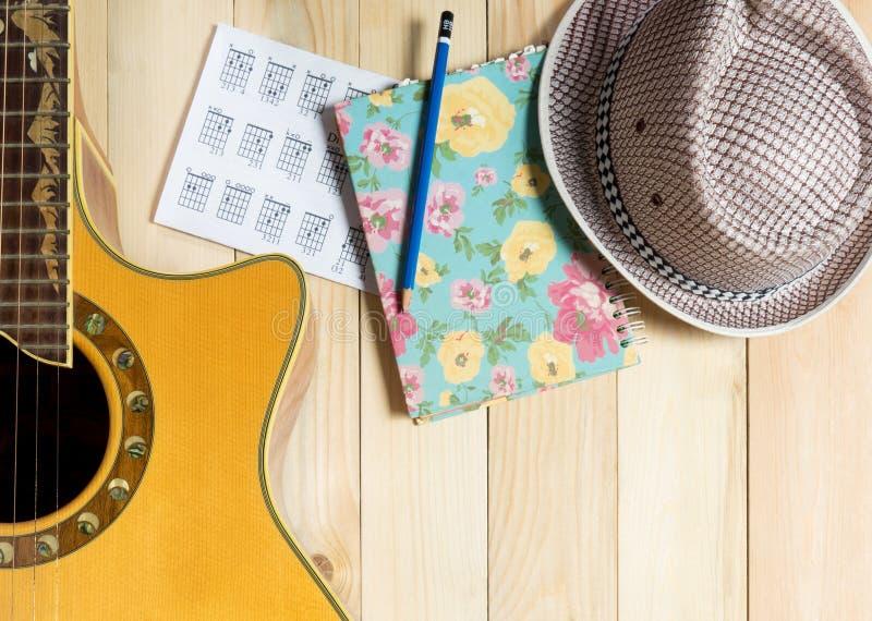 Сочинительство музыки шляпы музыки и лета гитары на древесине стоковая фотография rf