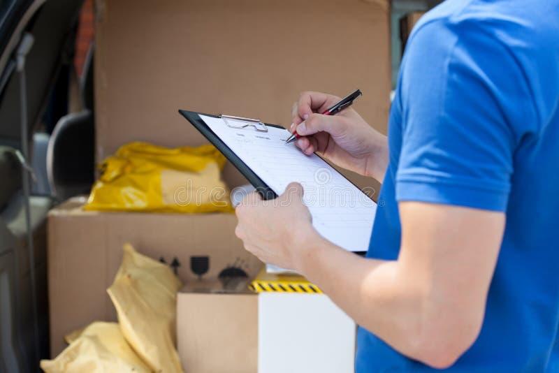 Сочинительство руки курьера на доске сзажимом для бумаги стоковое изображение