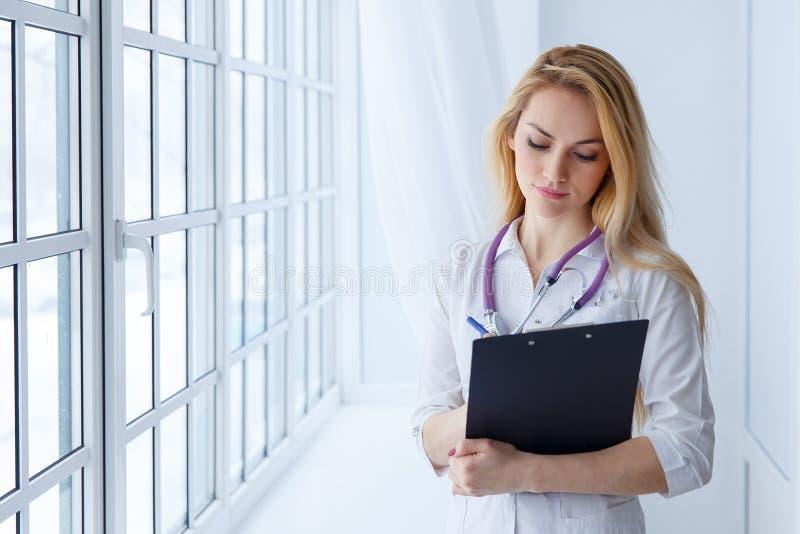 Сочинительство ручки удерживания доктора женщины на доске сзажимом для бумаги для принимать терпеливую обработку стоковая фотография rf