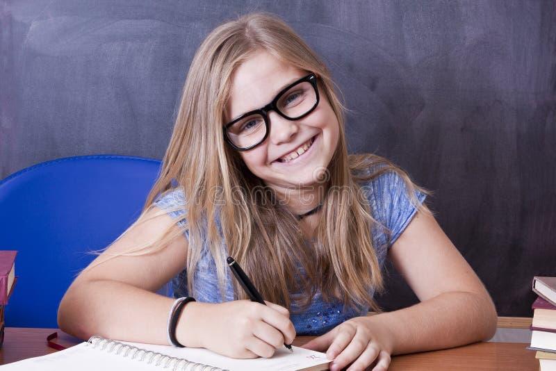 сочинительство таблицы школы девушки стоковое изображение