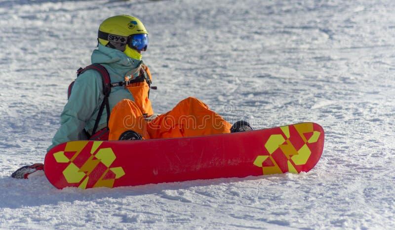 Сочи, Россия, 10-01-2018 Лыжный курорт Розы Khutor сидя snowboarder снежка стоковые изображения