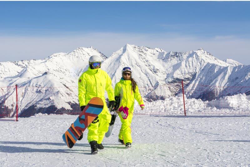 Сочи, Россия, 11-01-2018 Лыжный курорт Розы Khutor Snowboarders в ярких костюмах поверх розового пика на высоте 2320 определяют стоковое изображение