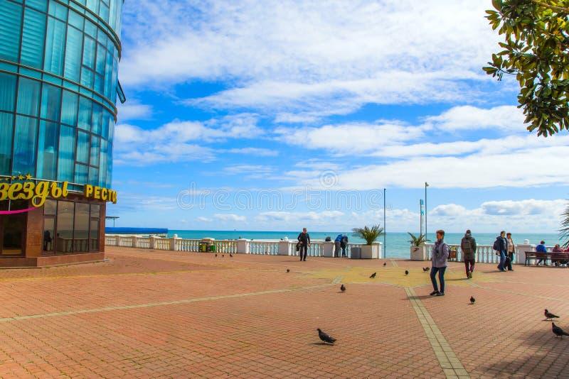 СОЧИ, РОССИЯ, 20-ОЕ АПРЕЛЯ 2019 - люди гуляя вдоль набережной Чёрного моря стоковое изображение