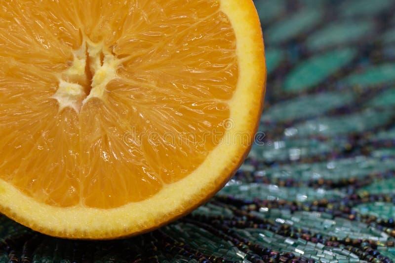 Сочная, суккулентная оранжевая половина на циновке Teal вышитой бисером стоковая фотография rf