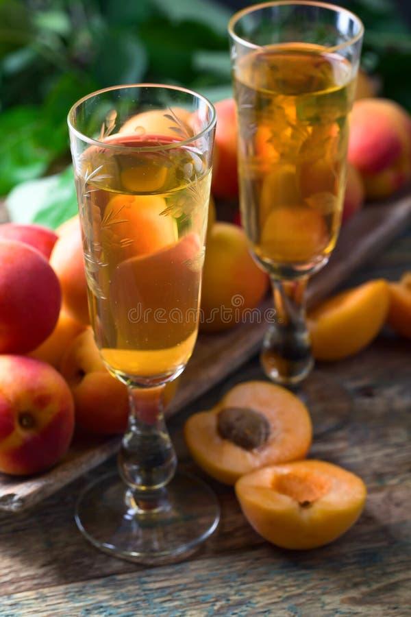 Сочные абрикосы с листьями и стеклом сладостного вина стоковые фото
