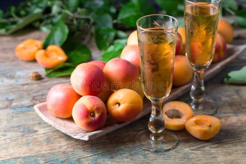 Сочные абрикосы с листьями и стеклом сладостного вина стоковое изображение