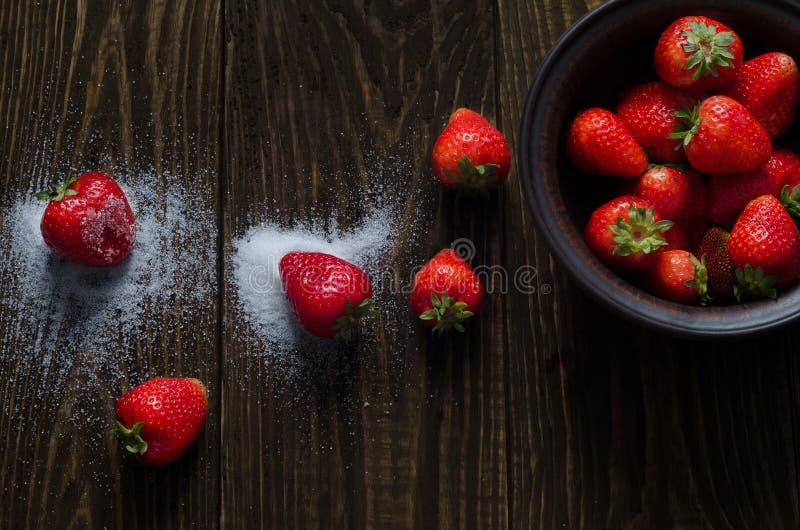 Сочные клубники в сахаре лежат на деревянной предпосылке стоковая фотография