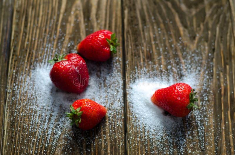 Сочные клубники в сахаре лежат на деревянной предпосылке стоковые фотографии rf