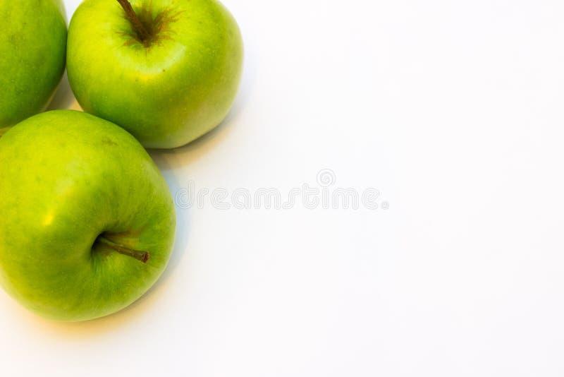 Сочные, очень вкусные, зрелые яблоки зеленеют на белой предпосылке стоковая фотография