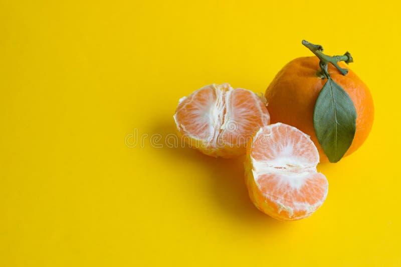 Сочный мандарин с лист и половиной 2 мандарина на желтой предпосылке стоковые изображения rf