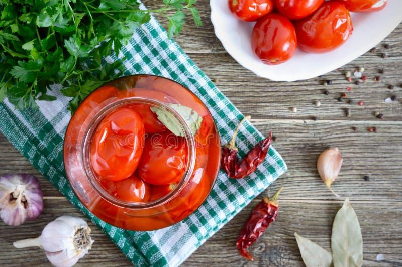 Сочувствительные острые маринованные помидоры с перцем и чесноком на деревянном столе Домашнее консервирование Овощистой растител стоковые изображения