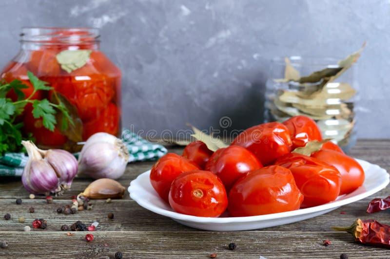 Сочувствительные острые маринованные помидоры с перцем и чесноком на белой тарелке на деревянном столе Домашнее консервирование О стоковое фото rf