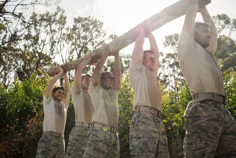 Солдаты нося журнал дерева стоковые изображения