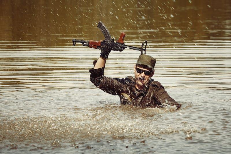 Солдат в равномерном заплывании в озере с штурмовой винтовкой стоковое фото