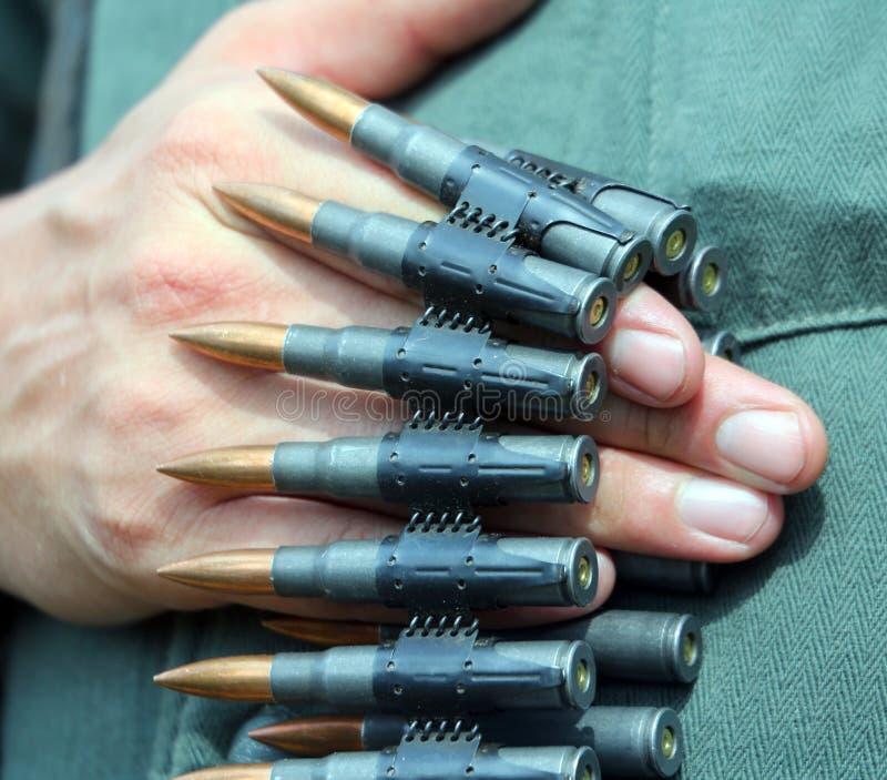 Солдат в форме с пулями в его рука готовая для того чтобы раскрыть огонь стоковое изображение