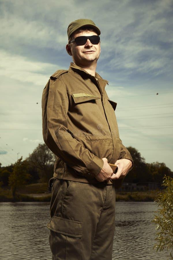 Солдат в чистой форме представляя в солнечных очках стоковое фото rf
