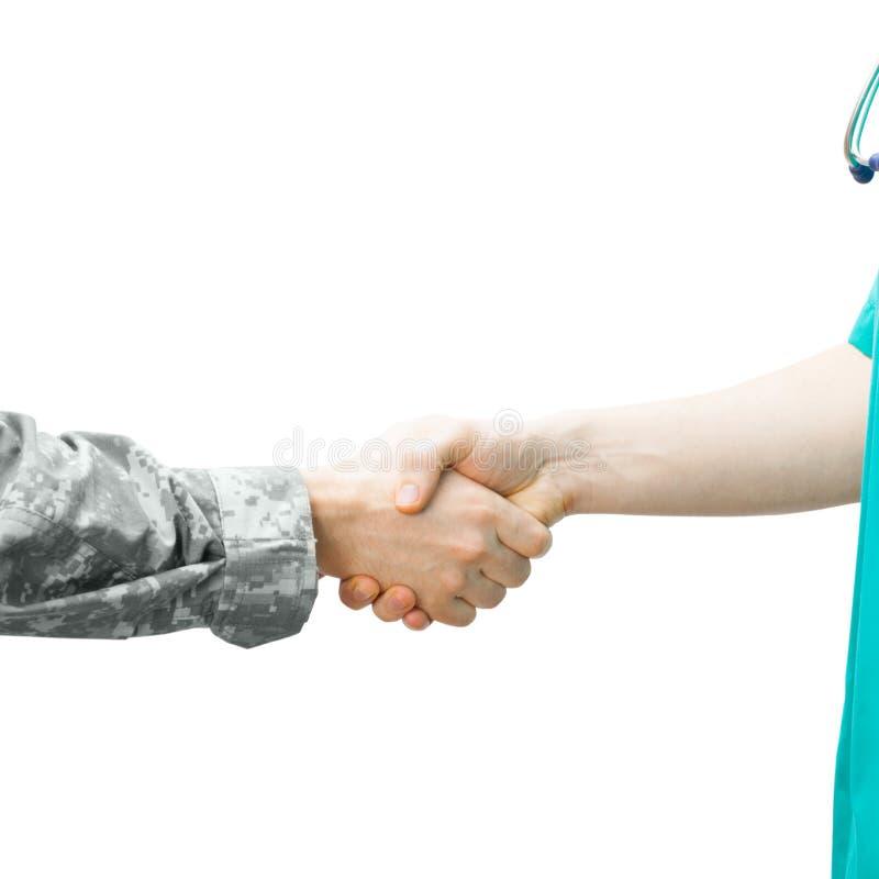 Солдат и доктор тряся руки на белой предпосылке - съемке студии стоковая фотография rf