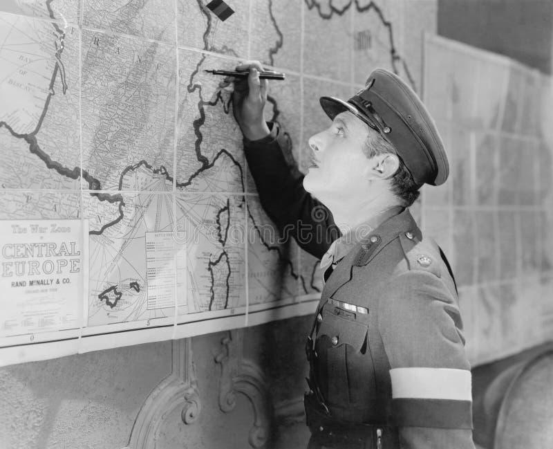 Солдат смотря карту отмечать его с ручкой (все показанные люди более длинные живущие и никакое имущество не существует Предписани стоковое фото rf