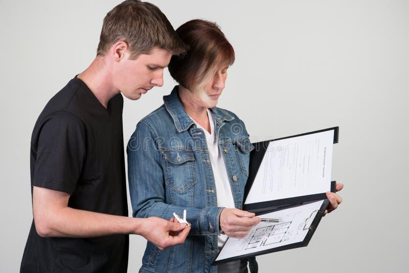Содержатель объясняет план здания к нанимателю, на gr стоковые изображения